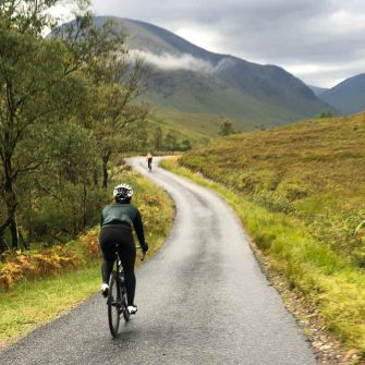 Cyclist riding up a hill in scotland