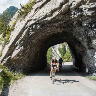 Cyclist through a rock tunnel on a cycling route in Switzerland