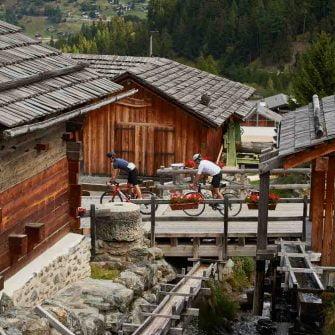 Cyclists cycling through ski resort of Grimentz, Switzerland