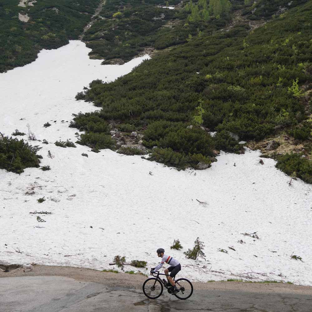 Cyclist surrounded by snow on the Vrisc Pass in Slovenia